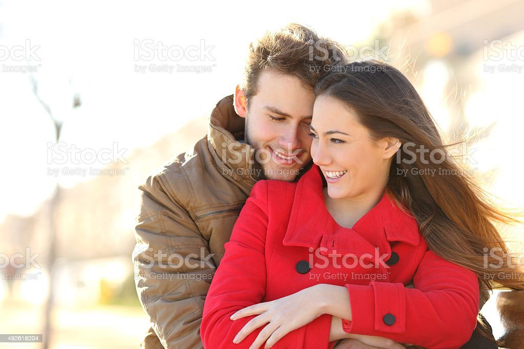 Couple dating and hugging in love in a park stock photo