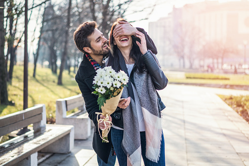 Young man surprising his girlfriend with white flowers bouquet