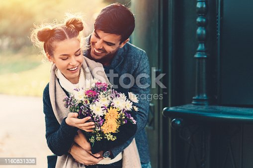 Young man giving flowers to his girlfriend on Valentine's day