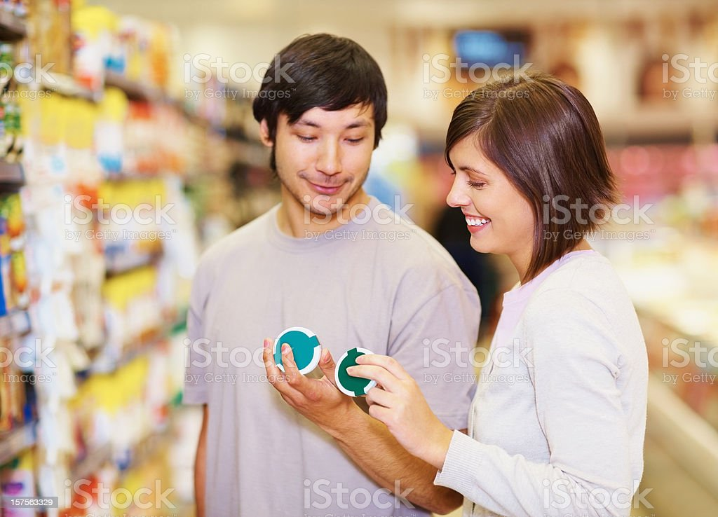 Couple deciding on a product to purchase at the supermarket royalty-free stock photo