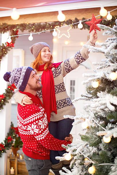 paar dekorieren weihnachtsbaum in front of house. - vorbau dekor stock-fotos und bilder