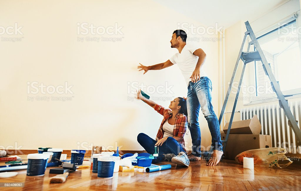 Couple decoration their apartment. Closeup of early 30's couple making decisions about what color their walls should be. They are in empty bedroom brainstorming about the design and colors, many paint cans are on the floor next to them. 20-29 Years Stock Photo