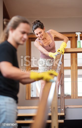 Two people disinfecting the railings in their home