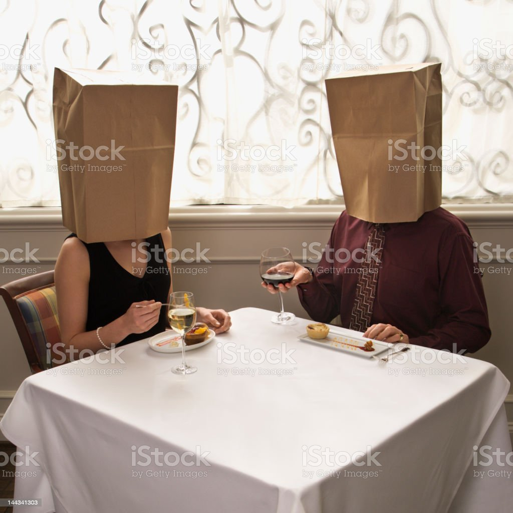 Couple dining wearing bags on heads. stock photo