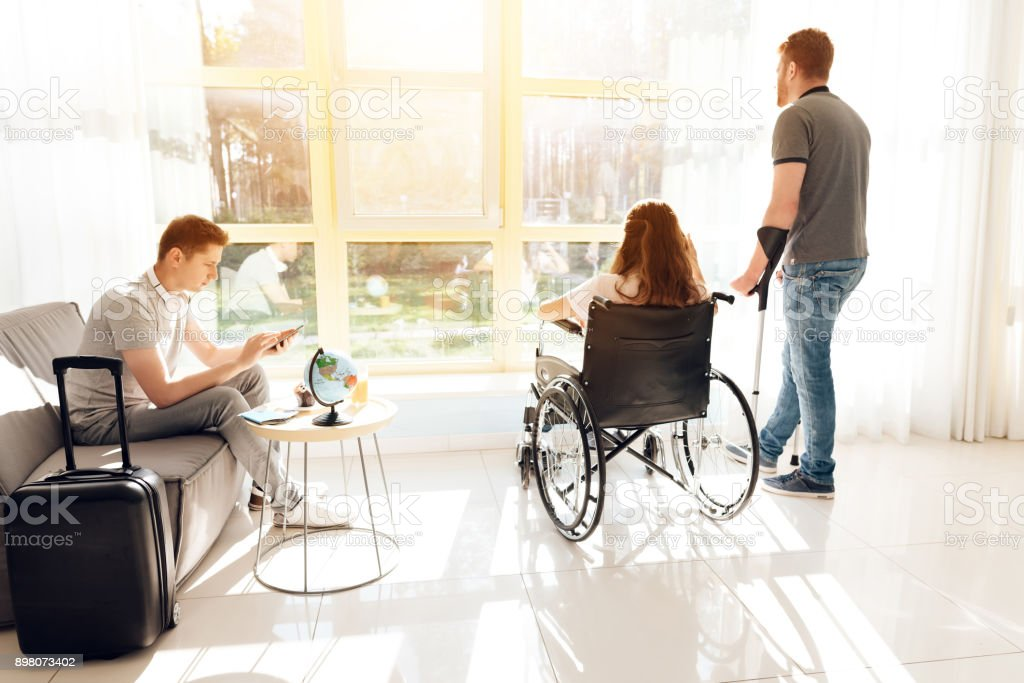 Couple disabled in the airport lounge. A girl in a wheelchair and a guy on crutches are traveling. stock photo