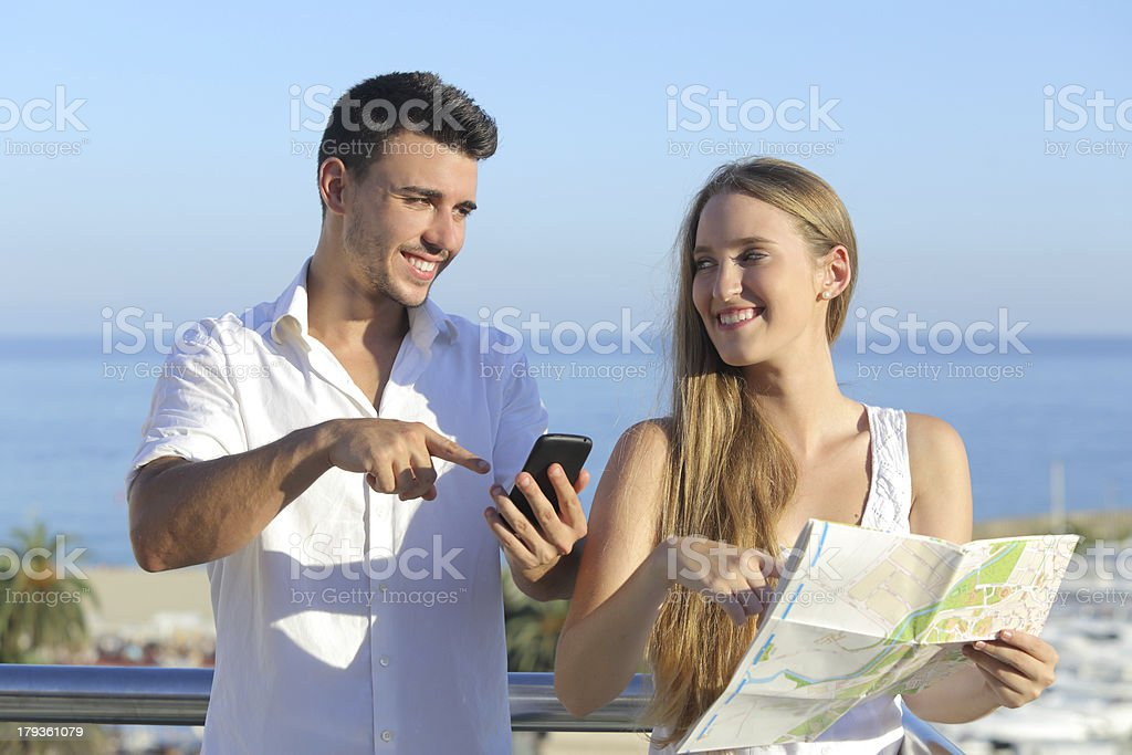 Couple discussing map or smartphone gps on vacations royalty-free stock photo