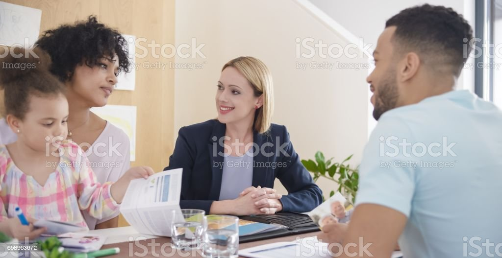 Couple discussing with insurance agent stock photo