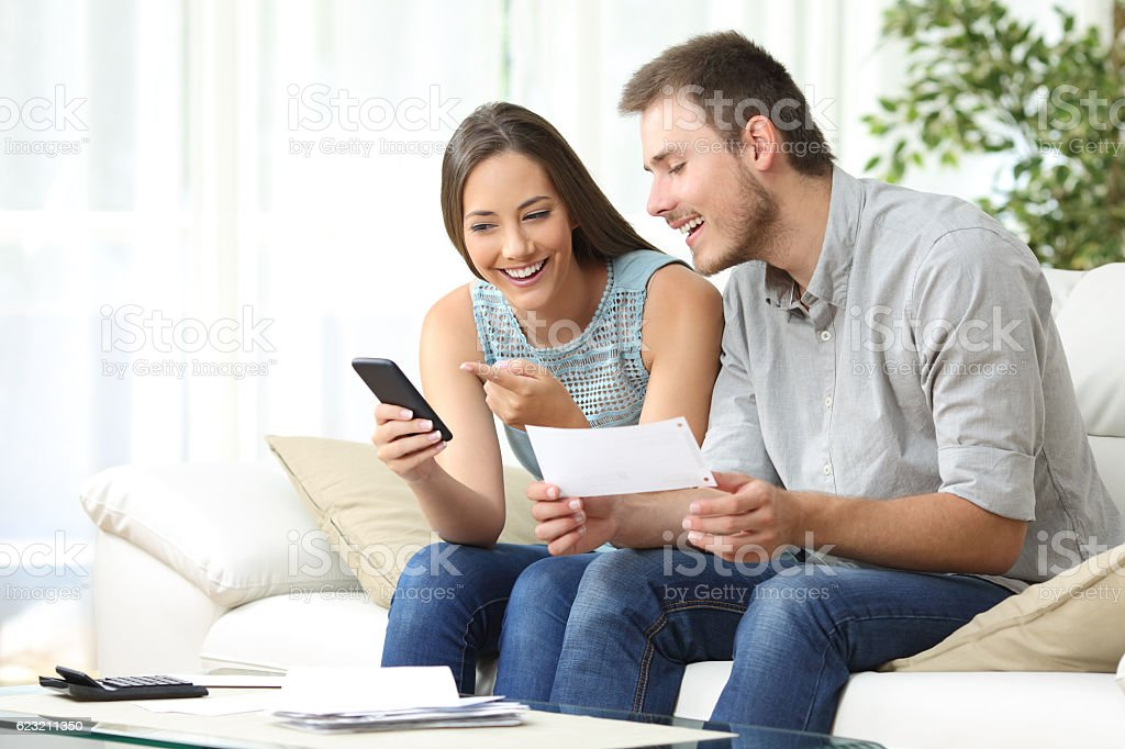Couple doing accounting with a phone bank app stock photo