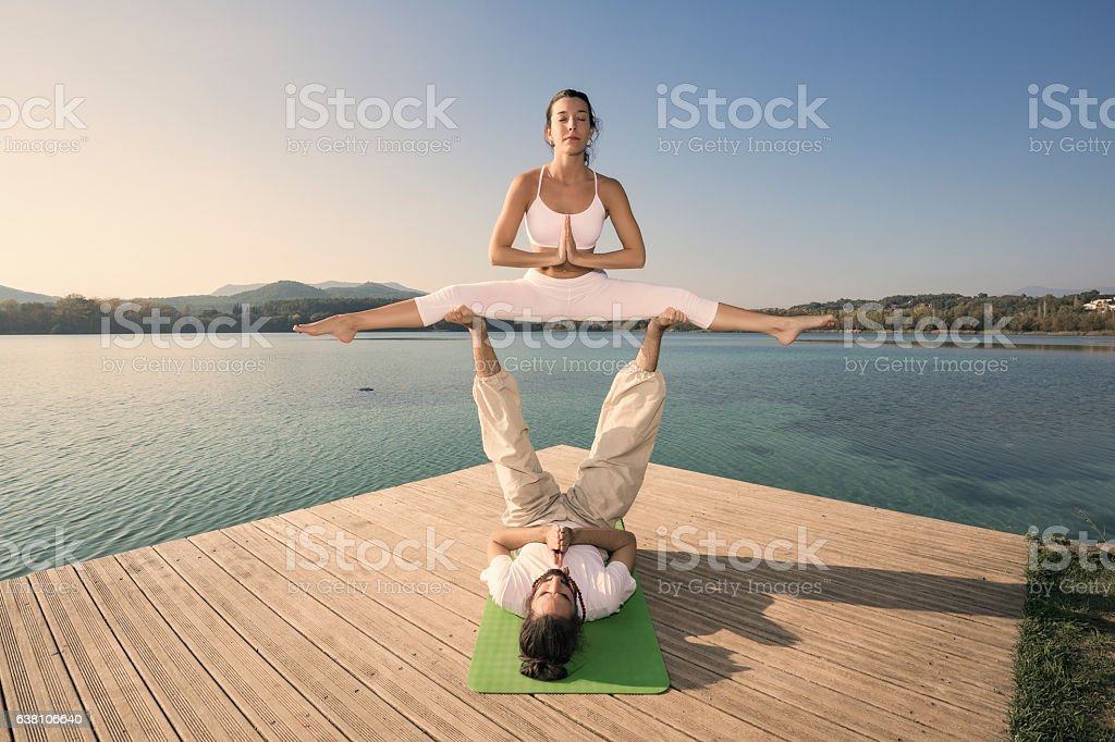 Couple doing acroyoga in nature stock photo