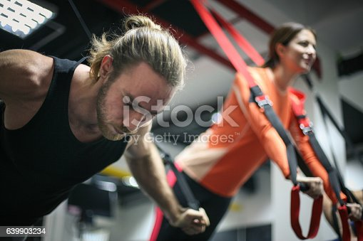 istock Couple doing exercises in a gym with straps. 639903234