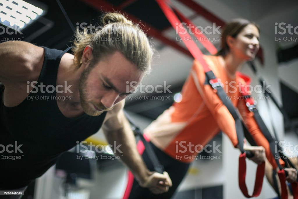 Couple doing exercises in a gym with straps. - foto de stock