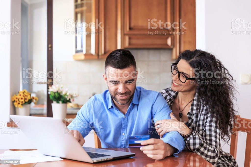 Smiling couple doing home budgeting, using laptop.