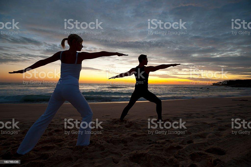 Couple doing yoga on the beach royalty-free stock photo