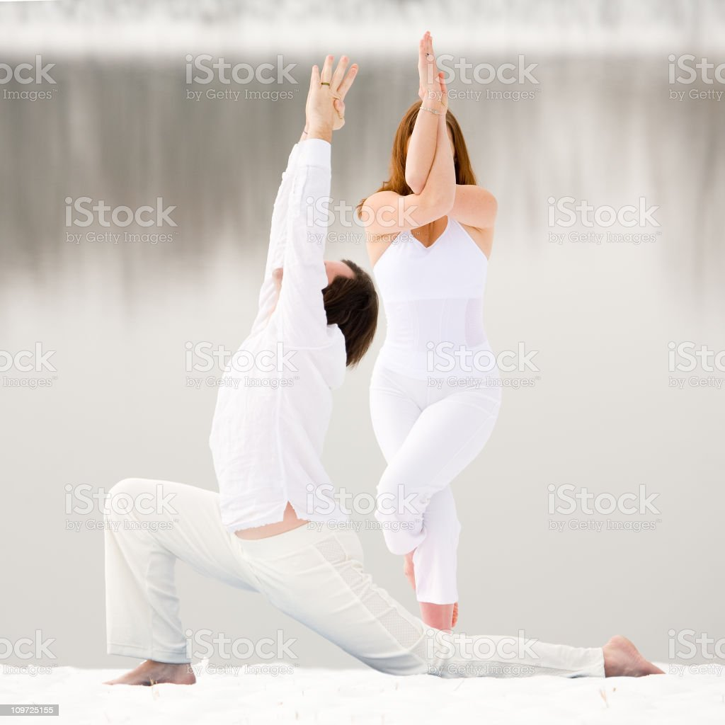 Couple Doing Yoga Poses in the Snow royalty-free stock photo