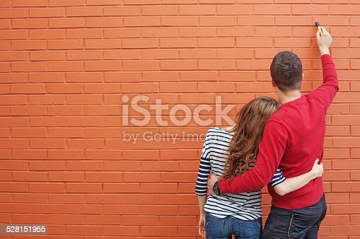 istock Couple drawing on a brick wall 528151955