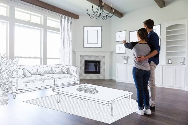 Couple dream in their new home A young couple stand in the empty living room of their new home and imagine the room decor and furniture placement. home improvement stock pictures, royalty-free photos & images