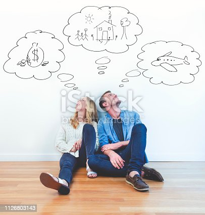Couple dreaming of family, wealth and travel. They are sitting together imagining a new house; money and overseas travel. They are happy and smiling