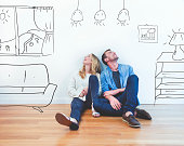 Couple dreaming of their new house. They are sitting on a wooden floor imagining their new home with furniture in it. The house is currently empty. They are booth looking up and smiling happily.