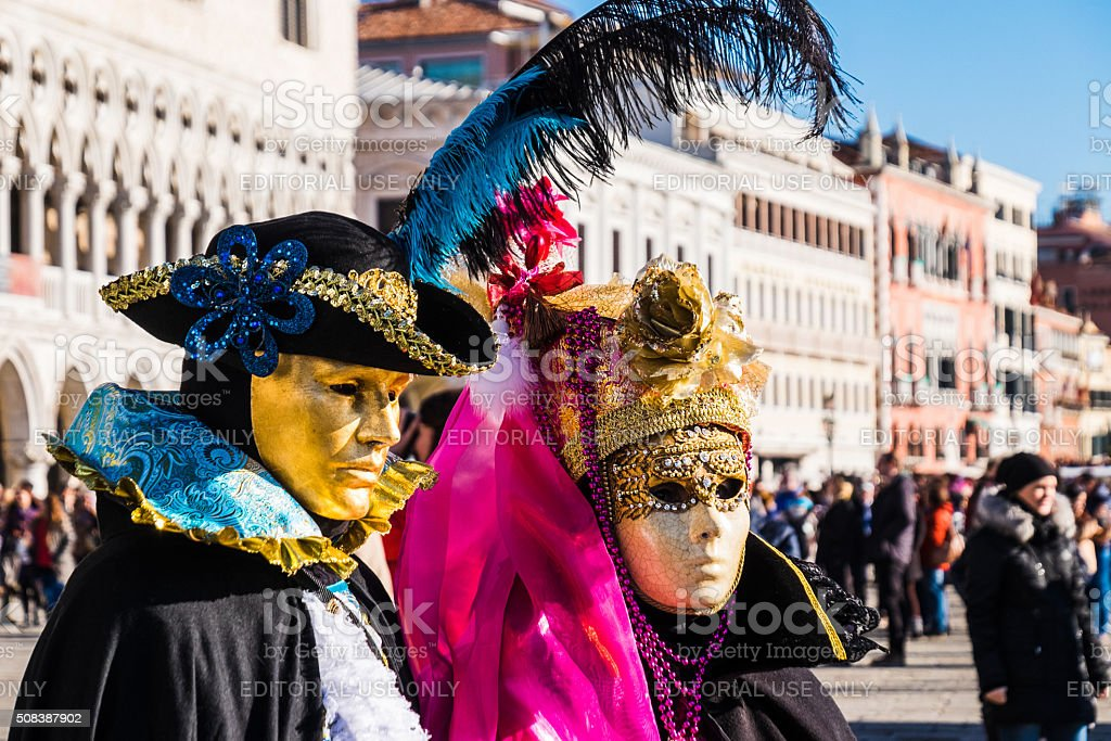 Couple dressed in carnival costumes pose for photograghers, Venice stock photo