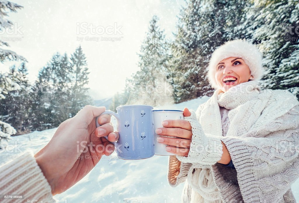 Couple drink a hot tea on winter forest glade stock photo