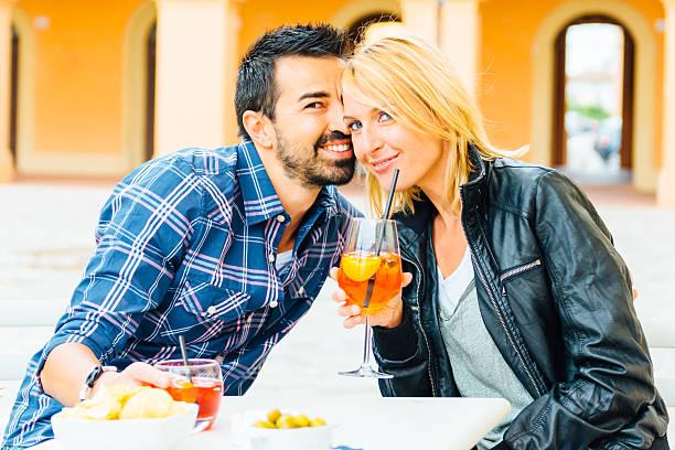 Coppia bere aperitivo al pub o bar insieme all'aperto - foto stock
