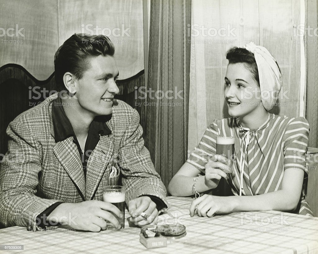 Couple drinking beer at bar table, (B&W) stock photo