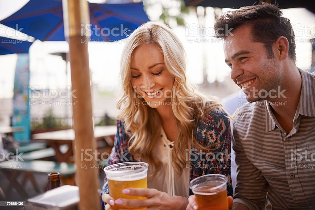 couple drinking beer at outdoor bar stock photo