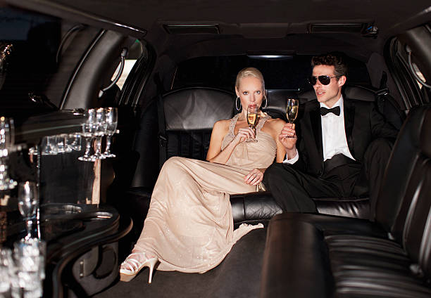 Couple drinking champagne in limo  Fame stock pictures, royalty-free photos & images