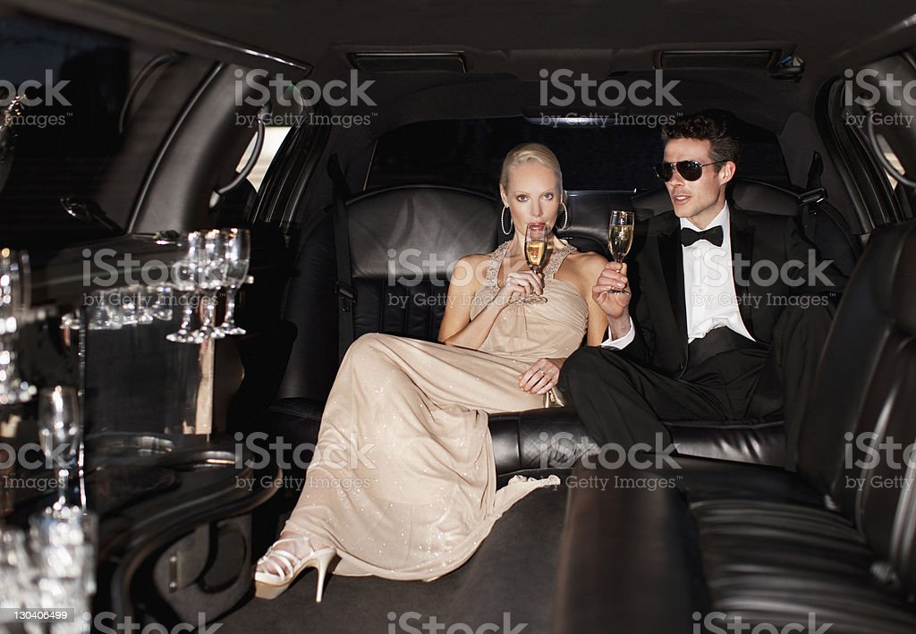 Couple drinking champagne in limo stock photo
