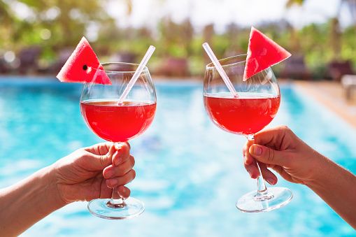 couple drinking cocktails near luxurious swimming pool in hotel