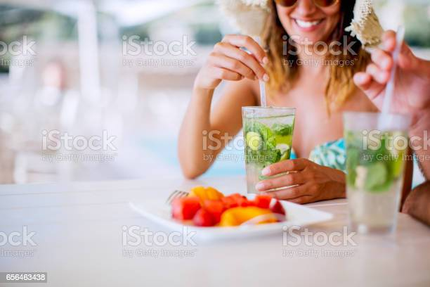 Photo of Couple drinking cocktails near pool