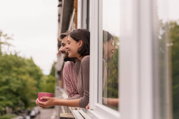 Couple drinking coffee and looking through the window stock photo