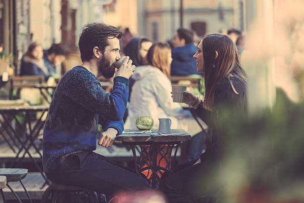 a couple drinking coffee at a picnic table in stockholm - couple lap stock photos and pictures