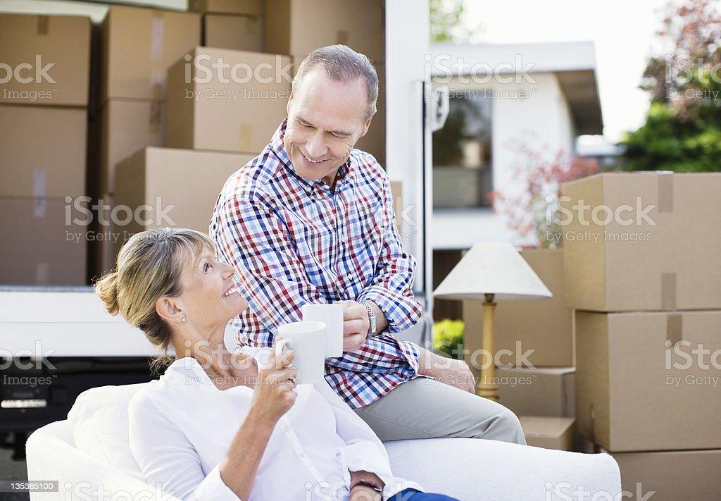 Couple drinking coffee near moving van royalty-free stock photo