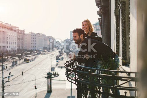 Couple on hotel balcony drinking coffee and enjoying the view of the city