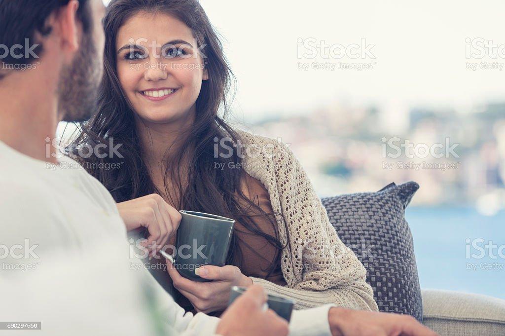 Couple drinking coffee on the sofa. Стоковые фото Стоковая фотография