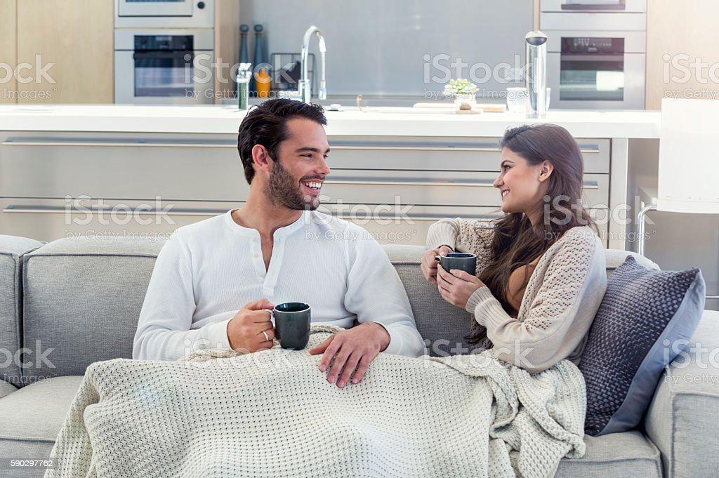 Couple drinking coffee on the sofa. royaltyfri bildbanksbilder