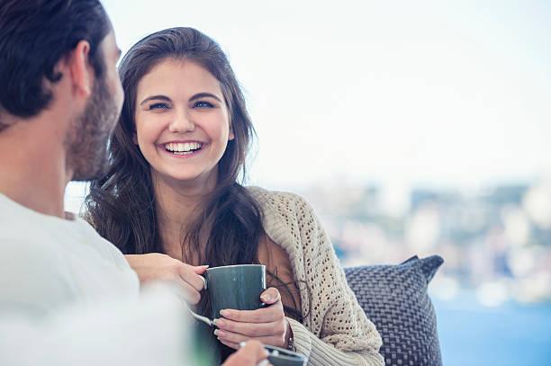Couple drinking coffee on the sofa. - foto de stock