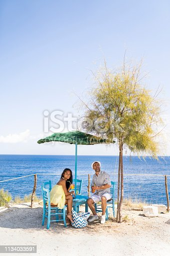Couple enjoying vacations, sitting in beach cafe.