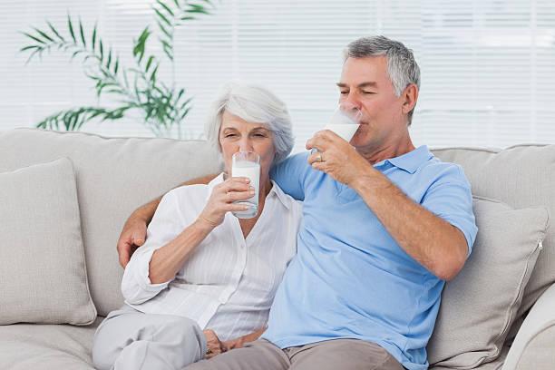 couple drinking glasses of milk sitting on the couch - calcium stockfoto's en -beelden