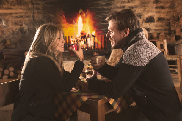 Couple drinking hot beverages in cafe in winter stock photo