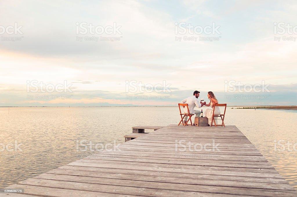 Paar trinken Rotwein im Meer an einem Anlegesteg – Foto