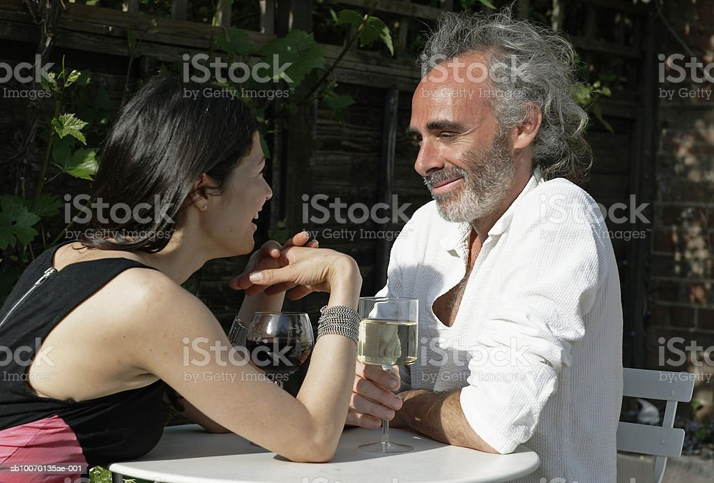 Couple drinking wine at outdoor table royalty-free stock photo