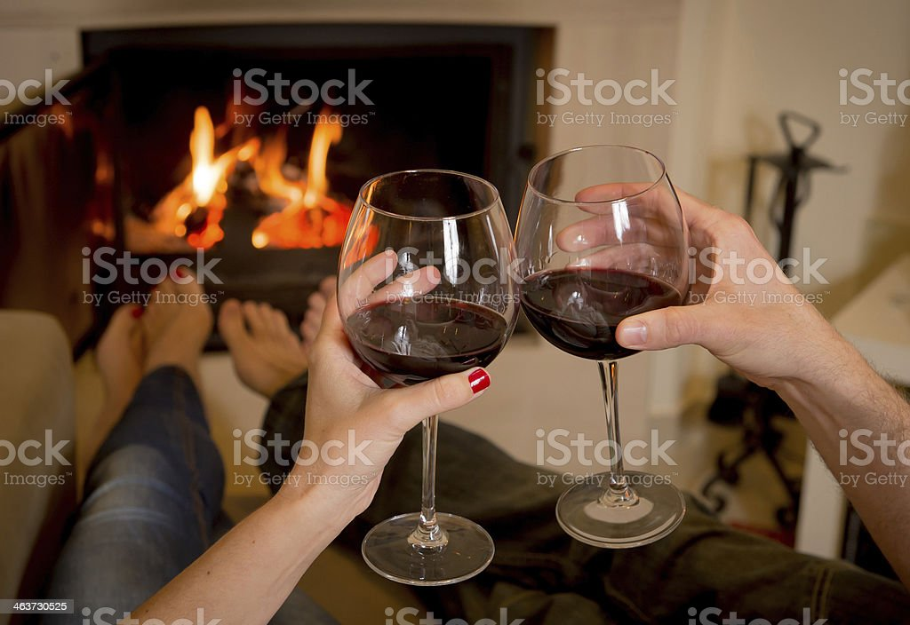 couple drinking wine in front of a fire stock photo