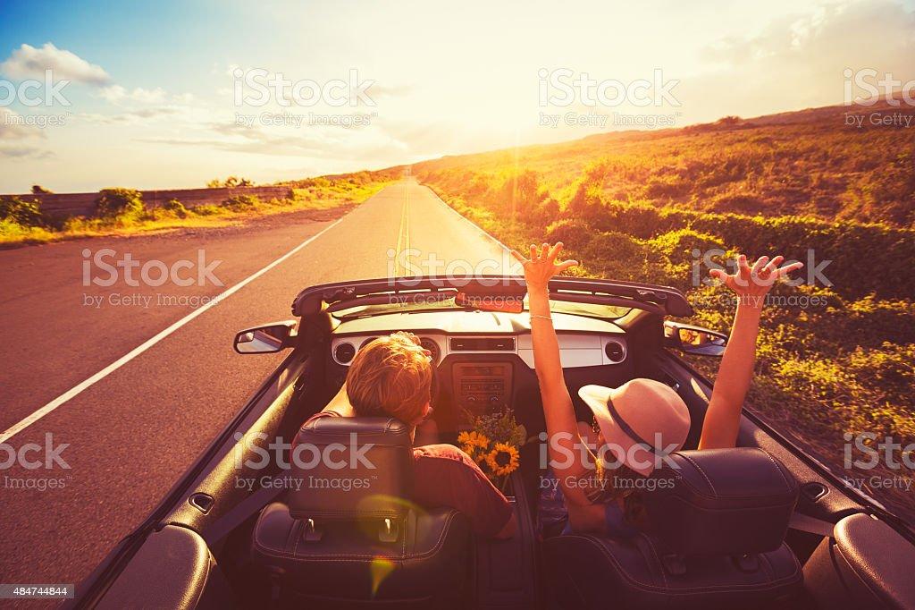 Couple en voiture décapotable au coucher du soleil - Photo