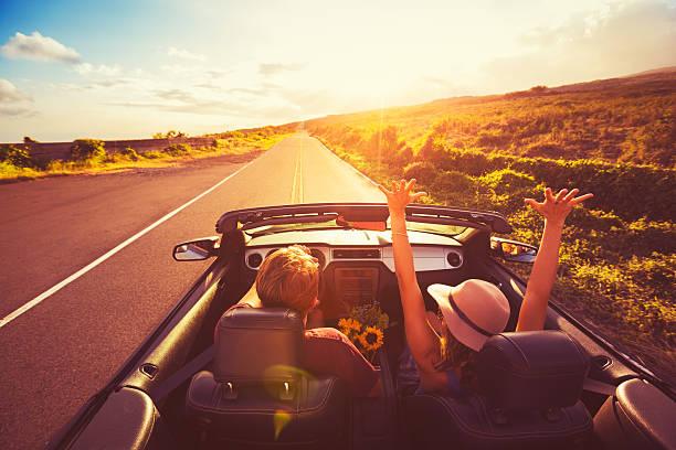 Paar fahren Convertable bei Sonnenuntergang – Foto