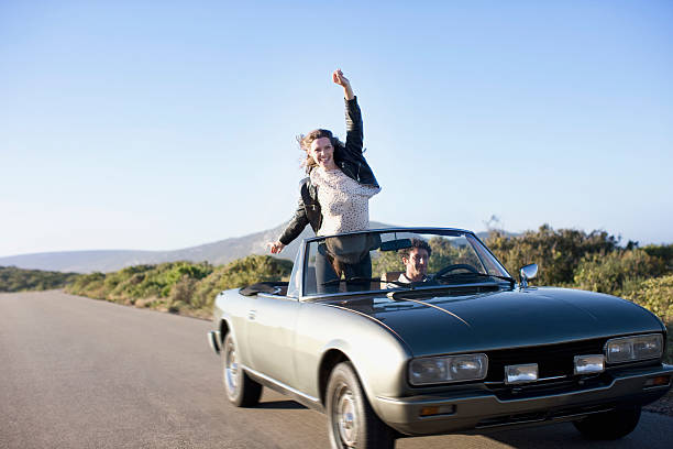 Couple driving in convertible stock photo