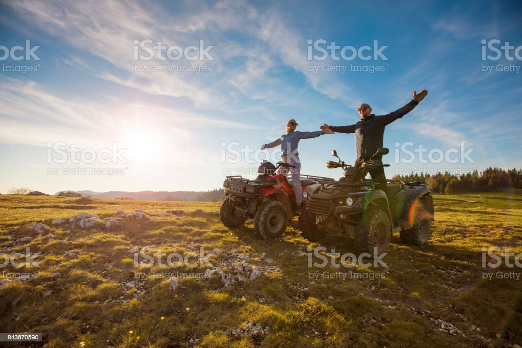 Couple driving off-road with quad bike or ATV stock photo