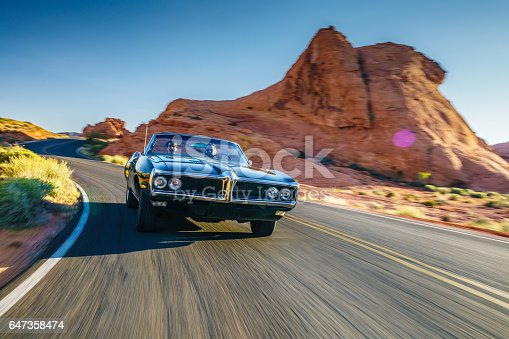 istock couple driving together in cool vintage car through desert 647358474