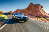 couple driving together in cool vintage car through desert at high speed.